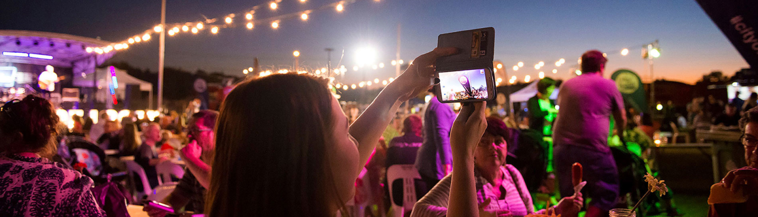 Woman taking a picture using her phone at festival
